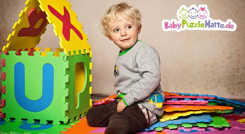 kleiner Junge baut aus Puzzlematte ein Häußchen