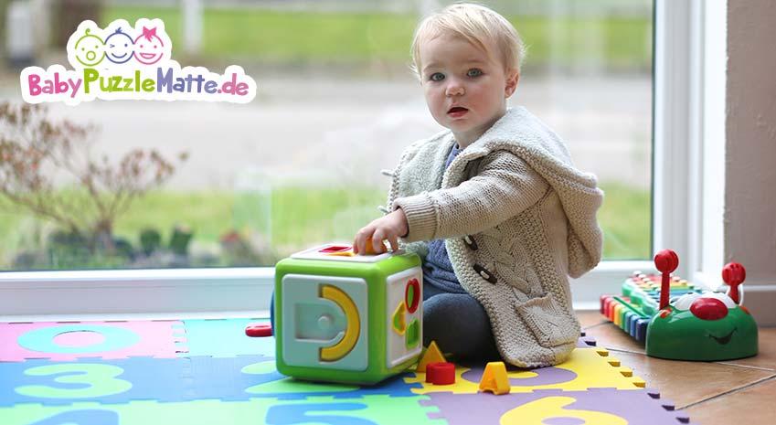 Kleinkind oder Baby Puzzleatte mit Spielzeug vor Fenster