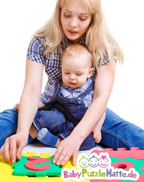 Mutter und Kind spielen auf einer Puzzlematte wie von Deuba