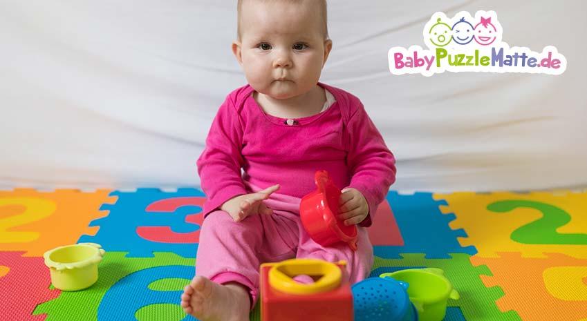 Baby in rosa Strampler spielt auf eine Puzzlematte wie von Prinzbert
