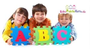 Kinder halten Puzzlematte ABC in den Händen hoch