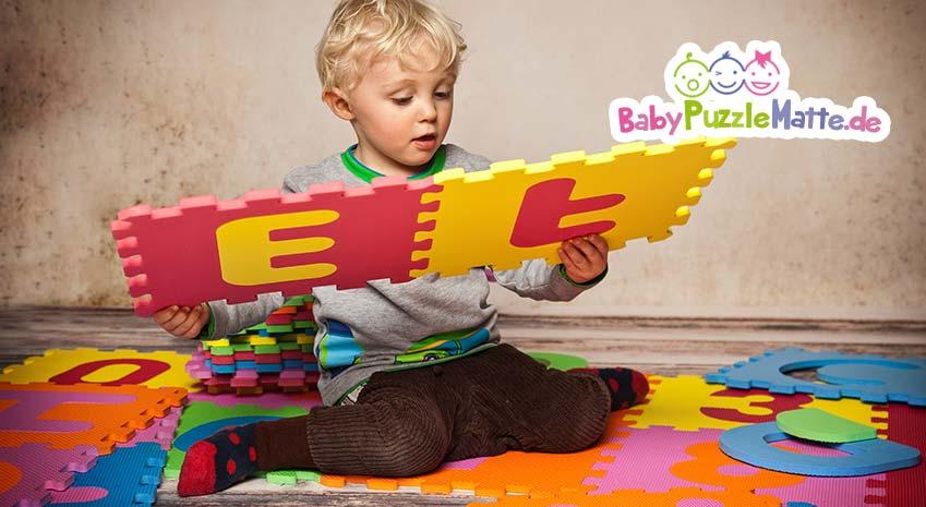 Kind spielt und lernt mit Puzzlematte Buchstaben