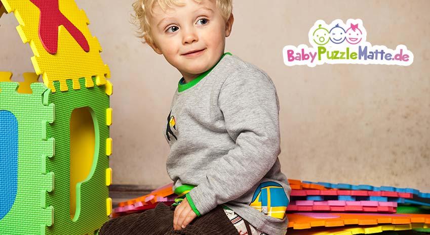 Puzzlematte Junge spielt mit den Puzzleteilen und baut daraus ein Haus