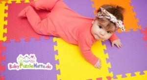 Puzzlematte mit Baby, das über die bunten Puzzle Felder krabbelt