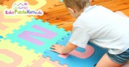 Wie sollte man eine Puzzlematte reinigen. Hier mit Kind beim auslegen der Puzzlematten Teile