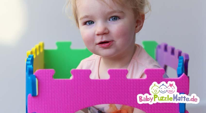 Kleinkind spielt mit seiner Puzzlematte rosa