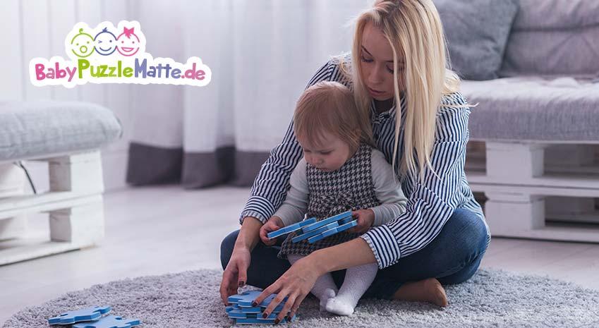 Mutter spielt mit ihrem Kind auf einer Puzzlematte zum aufrollen